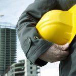 worker getting ready to wear helmet